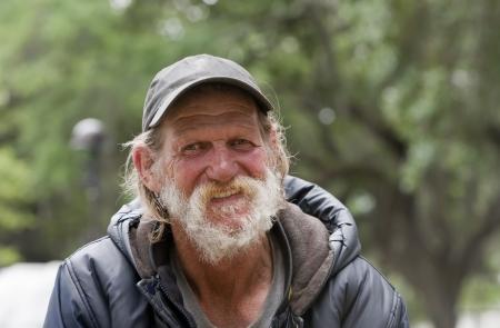 vagabundos: Feliz el hombre sin hogar sonriendo Foto de archivo