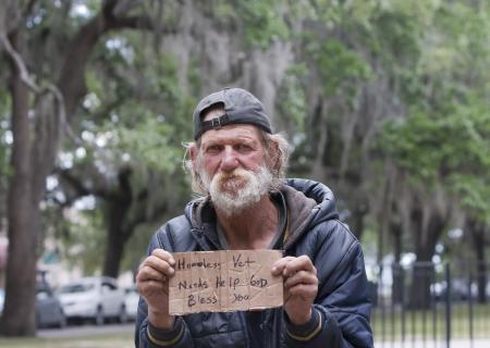 gente pobre: Hombre sin hogar celebración de firmar
