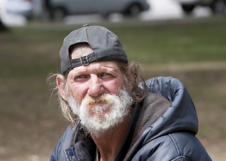 Homeless man sitting outdoors during the day Stockfoto