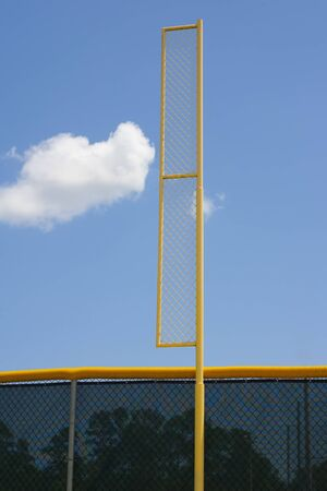foul: Yellow baseball foul pole with metal netting