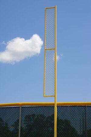 Yellow baseball foul pole with metal netting