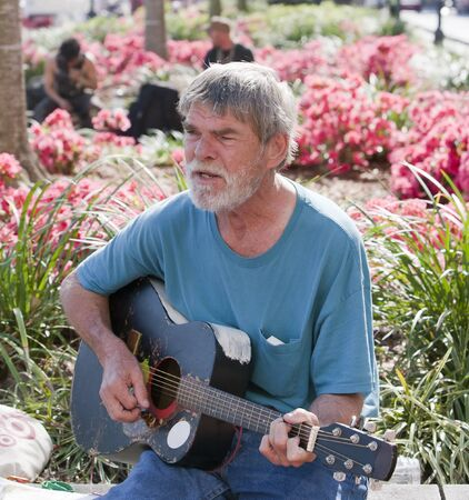 Active elderly man playing guitar outside during the day photo