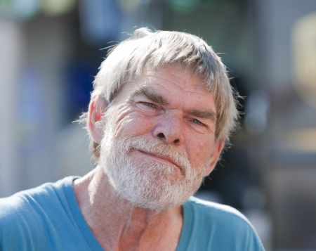 homeless: Sonriendo al aire libre, hombre de alto nivel durante el d�a