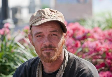 昼間に外に座っている若いホームレスの男性 写真素材