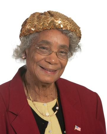 Portret lachende oudere Afro-Amerikaanse dame, tegen een witte achtergrond Stockfoto