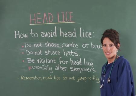 School nurse teaching about head lice on chalkboard of classroom. Foto de archivo
