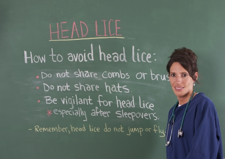 school nurse: School nurse teaching about head lice on chalkboard of classroom. Stock Photo
