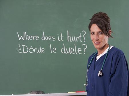 Nurse teacher translating English to Spanish on chalkboard of classroom. Focus is on teacher.