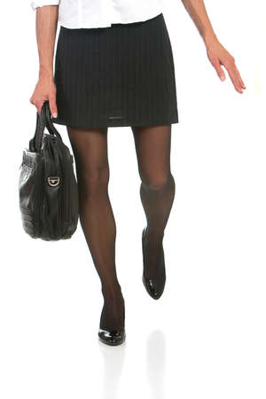 business woman with beautiful legs in a hurry. Shot against white background. photo