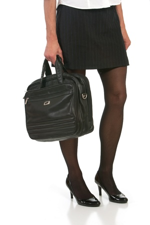 short skirt: low angle of woman with beautiful legs holding briefcase. Shot against white background.