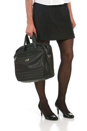 falda corta: ángulo bajo de la mujer con las piernas hermosas que sostienen maletín. Disparo contra el fondo blanco.