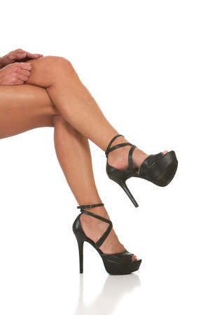 female stripper: woman with sexy high heels with straps sitting. Isolated against white background.