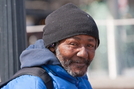 homeless person: Happy homeless african american man outdoors during the day.