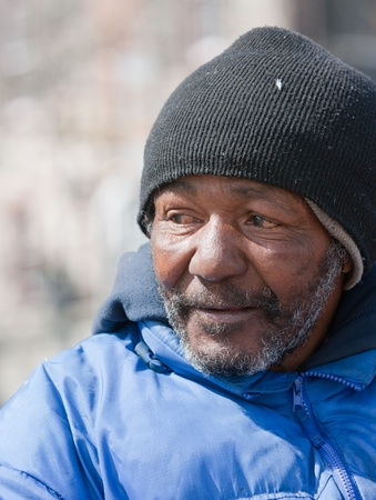 hobo: Side angle of homeless african american man outdoors during the daytime.