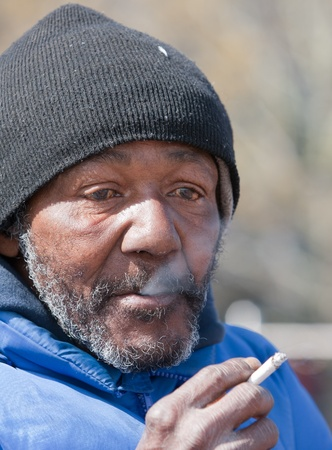 hobo: Homeless man smoking a cigarette outdoors during the day.