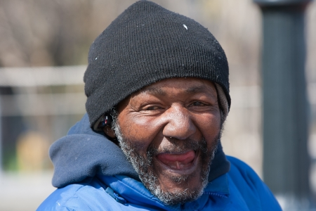 hobo: Happy and smiling homeless african american man outdoors during the day.
