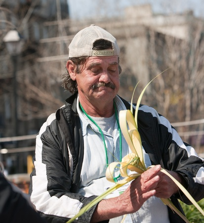 Homeless man working and making a rose out of a piece of palm.  Stock Photo