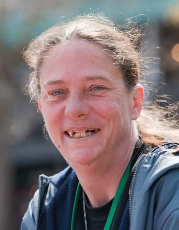 vagabundos: Mujer sin hogar que sonríe con los dientes en mal estado. Al aire libre durante el día. Foto de archivo