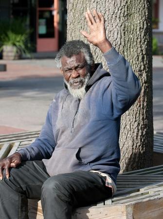 屋外に座りながら手を振っている高齢者アフリカ系アメリカ人のホームレスの男性