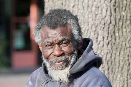 Portrait of African merican homeless man in black in white outdoors