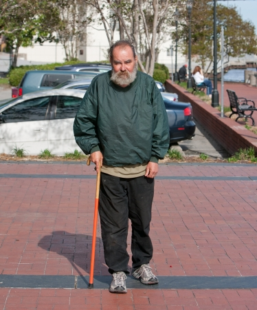 hobo: Handicapped homeless man walking with cane for support outdoors
