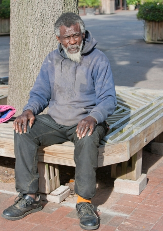 homeless people: Dirty elderly African American homeless man sitting outside