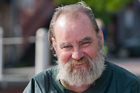 dirty old man: Homeless man with a smile on his face  Outdoors during the daytime