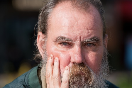 old man beard: Portrait of homeless man with short fingernails outdoors during daytime  Stock Photo