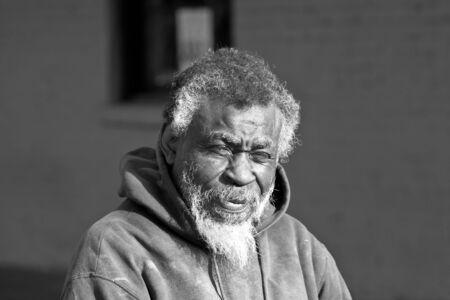 Portrait of elderly African American homeless man in black in white outdoors