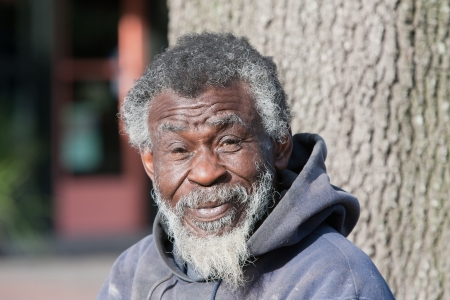 Portrait of old homeless African American man outdoors during daytime Foto de archivo