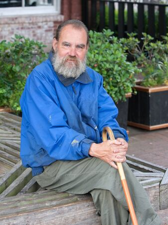 Elderly homeless man sitting with cane outside