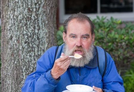 Portrait of poor homeless man eating food