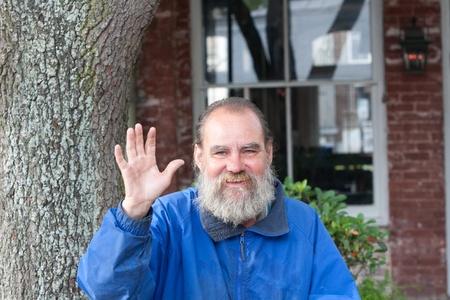 昼間の間に屋外ながら手を振っているホームレスの男性