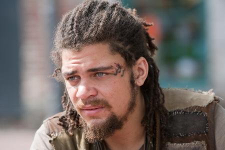 dreadlocks: Retrato de hombre rebelde joven con rastas y tatuajes