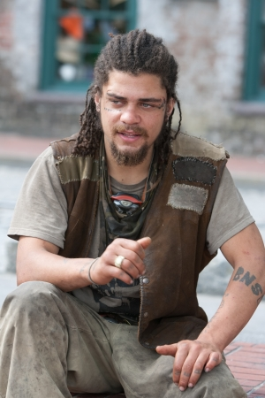 Rebel with dreadlocks and tattoos sitting outside Stock Photo