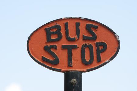 오래 된 검은 색과 오렌지색 금속 버스 정류장 기호 스톡 콘텐츠