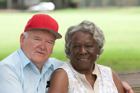 interracial marriage: Old multiracial couple outdoors during the summer Stock Photo