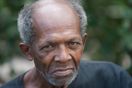 Old african american homeless man outdoors with sad eyes