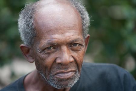 hombre pobre: Viejo hombre sin hogar afroamericano al aire libre con los ojos tristes Foto de archivo