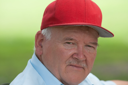 Portrait of old man with mustache outside during the day