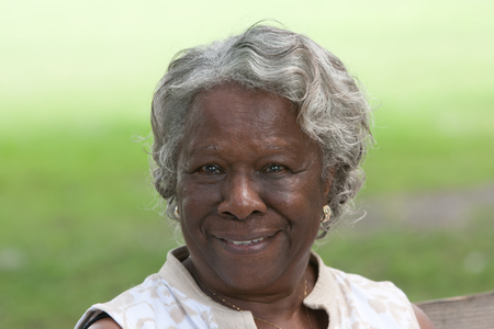 Happy old african american lady smiling outdoors during the day