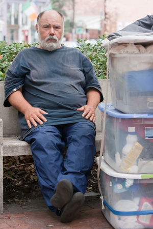 Homeless man sitting on bench with his possessions stacked beside him