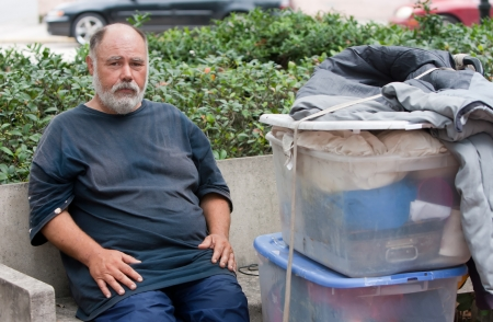 Poor homeless man on bench with possessions.