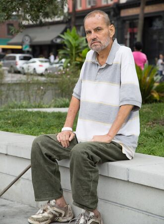 Homeless man sitting outdoors during the daytime