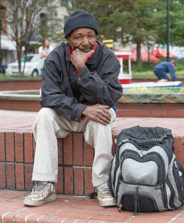 Homeless african american man sitting outdoors with backpack
