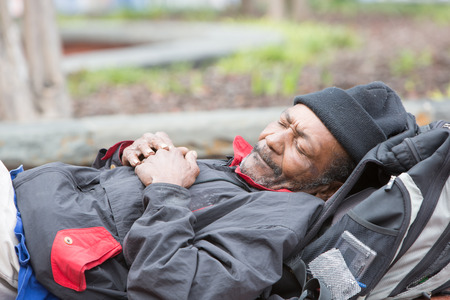 Old african american homeless man sleeping outside during the day