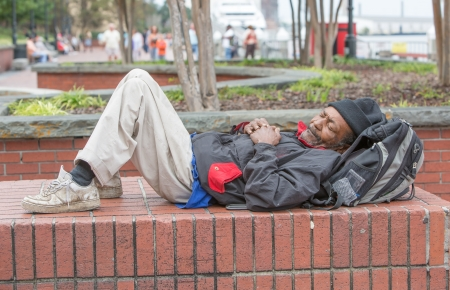 African american homeless man sleeping outside on bricks