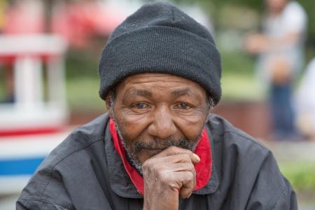 昼間に屋外に座って考えるホームレスの男性の肖像画