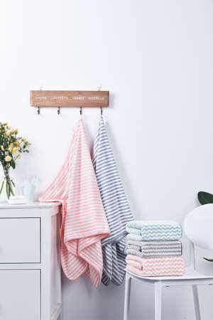 bath towels neatly folded on chair and hanging on wall mounted hook