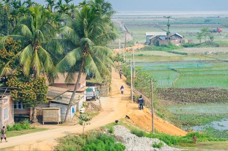 Aldea en Assam, India, con aldeanos caminando por la carretera, cerca de campos de arroz Foto de archivo